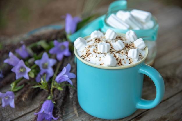Köstlicher cappuccino mit karamell und marshmallows in einem hellblauen becher.