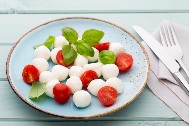 Köstlicher caprese-salat mit reifen kirschtomaten und mini-mozzarella-käsebällchen mit frischen basilikumblättern.