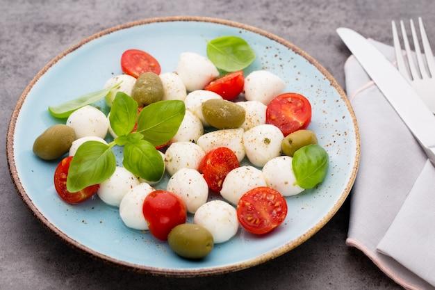 Köstlicher caprese-salat mit reifen kirschtomaten und mini-mozzarella-käsebällchen mit frischen basilikumblättern