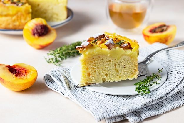 Köstlicher chiffon-kuchen mit puddingcreme und nektarinen mit kräutertee und thymian.