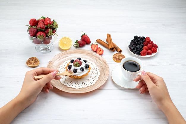 Köstlicher cremiger kuchen mit beeren, die von frau mit zimtkaffee auf hellweißem schreibtisch, kuchen süße fotofarbe essen