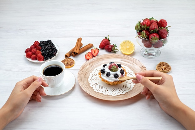 Köstlicher cremiger kuchen mit beeren, die von frau mit zimtkaffee auf hellweißem schreibtisch, kuchenfotofarbe gegessen werden