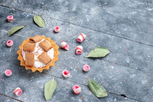 Köstlicher cremiger kuchen mit keksen zusammen mit geschnittenen bonbons auf grauer, kuchensüßer backcreme