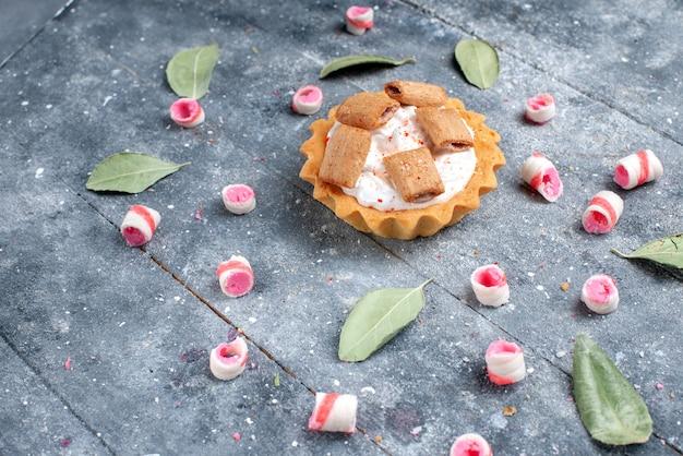 Köstlicher cremiger kuchen mit keksen zusammen mit geschnittenen rosa bonbons auf grauer, kuchensüßer backcreme
