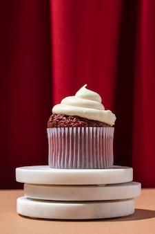 Köstlicher cupcake und roter vorhang