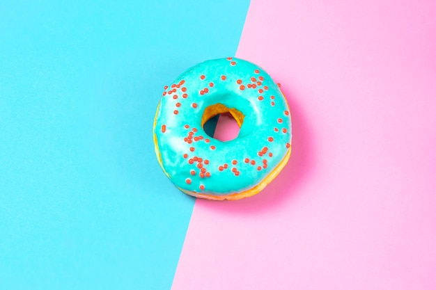 Köstlicher donut mit blauer glasur und besprühen auf einer blauen und rosa tabelle. konzept der süßen nahrung (nachtisch). draufsicht, flach zu legen