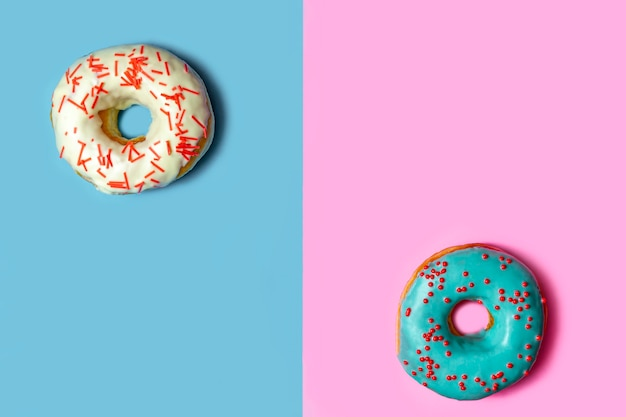 Köstlicher donut mit blauer glasur und besprühen auf einer blauen und rosa tabelle. konzept der süßen nahrung (nachtisch). draufsicht, flache lage, kopienraum.