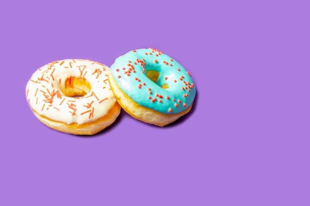 Köstlicher donut mit blauer glasur und besprühen nahaufnahme auf einer purpurroten tabelle. konzept der süßen nahrung (nachtisch).