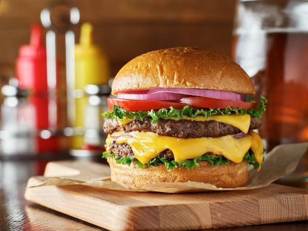 Köstlicher doppelter cheeseburger auf einem holzbrett