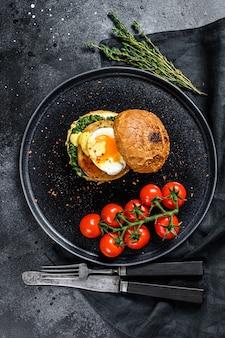 Köstlicher fishburger mit fischfilet, ei und spinat auf einem briochebrötchen