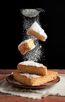 Köstlicher frisch gebackener biskuitkuchen mit zwei stück kuchen, die fallen und puderzucker darüber streuen