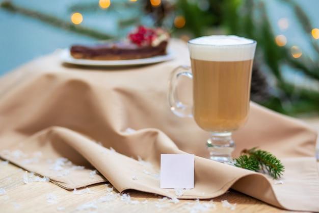 Köstlicher frischer festlicher morgencappuccinokaffee in einem glasschalen- und kuchennachtisch auf dem holztisch, den leuchtkäfern und den fichtenzweigen