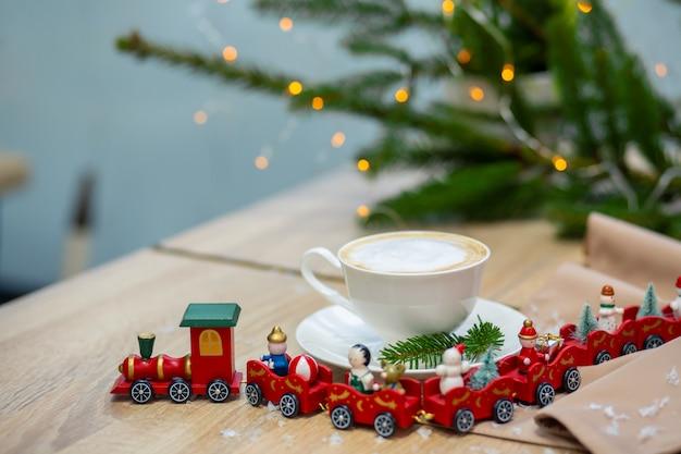 Köstlicher frischer festlicher morgencappuccinokaffee in einer keramischen weißen schale auf dem holztisch mit dekorativem weihnachtszug, roten ornamentals, leuchtkäfern und fichtenzweigen.