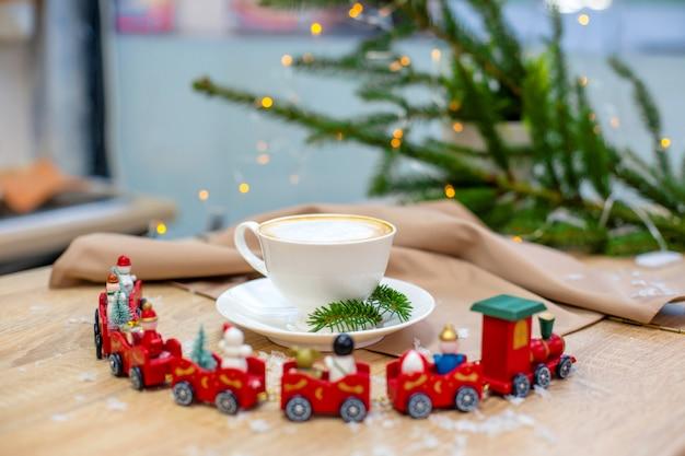 Köstlicher frischer festlicher morgencappuccinokaffee in einer keramischen weißen schale auf dem holztisch