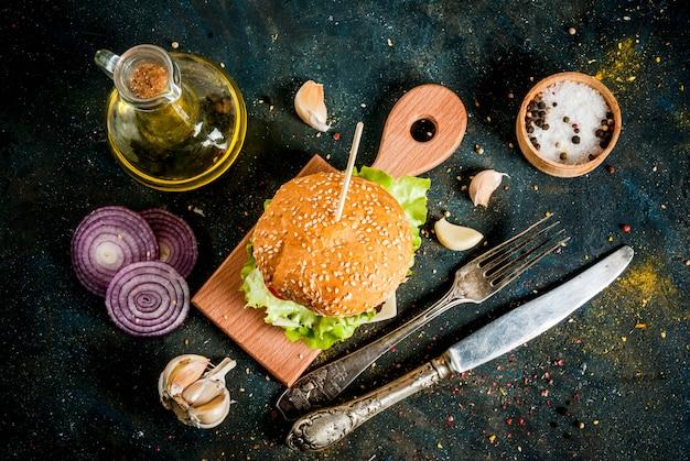 Köstlicher frischer geschmackvoller burger des ungesunden lebensmittels des schnellimbisses mit frischgemüse und käse des rindfleisch-koteletts auf dunkelblauem konkretem hintergrund