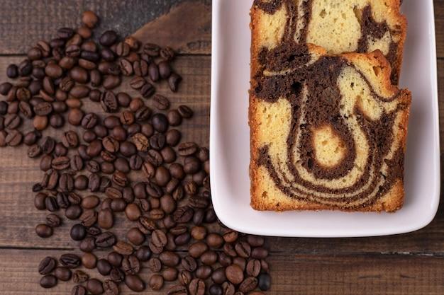 Köstlicher frischer kuchen in der weißen platte mit kaffeebohnen.