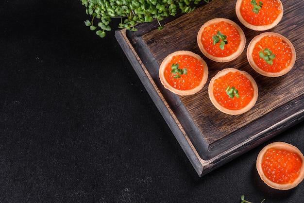 Köstlicher frischer roter kaviar auf einem dunklen betontisch. leckeres und herzhaftes frühstück