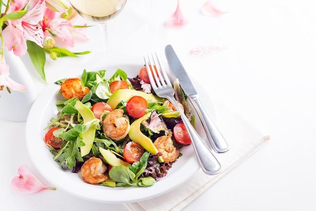 Köstlicher frischer salat mit garnelen, gemüse, gurke, avocado und tomate mit weißwein und blumen auf heller oberfläche