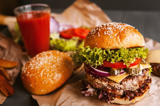 Köstlicher frischer selbst gemachter burger auf einem holztisch. neben der komponente zu burger, holzschalen, bratkartoffeln und chili. ein glas tomatensaft