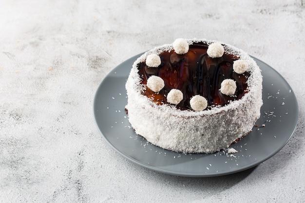 Köstlicher ganzer schokoladenkuchen auf teller mit kokosnussbonbons oben auf tisch auf marmorhintergrund. tapete für konditorei oder cafémenü. horizontal.