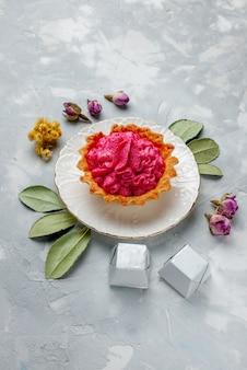 Köstlicher gebackener kuchen mit rosa sahne und pralinen auf leichter, süßer kuchencreme mit kuchenkeks