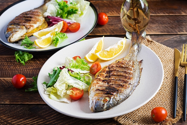 Köstlicher gegrillter dorado- oder seebrassenfisch mit salat, gewürzen, gegrillter dorada auf einem holztisch