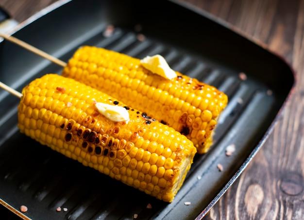 Köstlicher gegrillter mais mit butter und salz auf einer grillpfanne