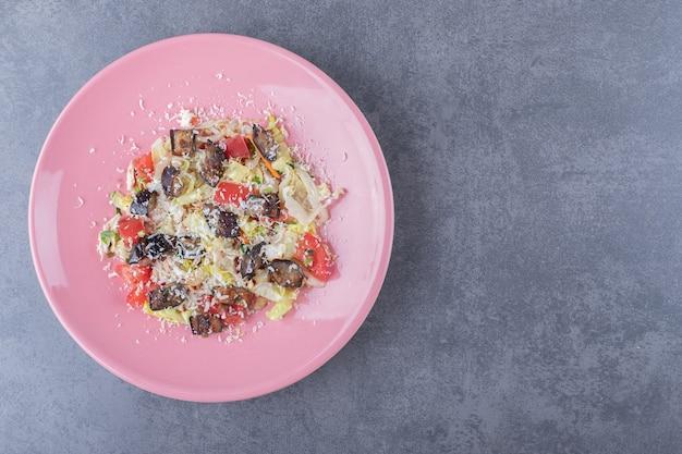 Köstlicher gemüsesalat auf rosa teller.
