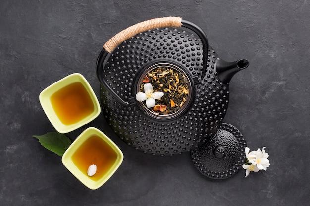 Köstlicher gesunder kräutertee in der schüssel mit schwarzer teekanne auf strukturiertem hintergrund