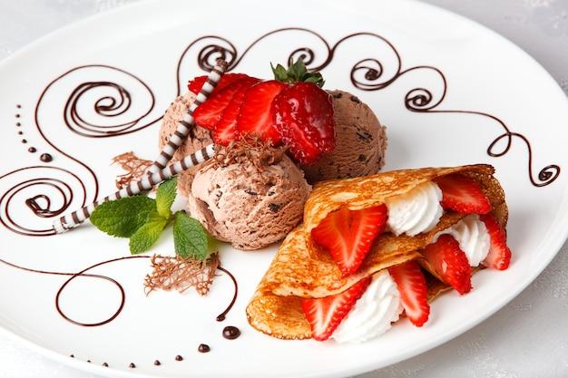Köstlicher goldener frisch gebackener erdbeercremepfannkuchen mit schokoladeneiscreme