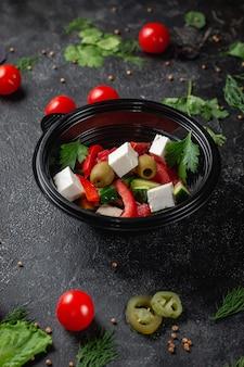 Köstlicher griechischer salat mit tomaten, oliven und frischen kräutern, ein frischer salat auf der speisekarte eines fast-food-restaurants auf einem dunklen steintisch. gesunde alternative zu fast food.