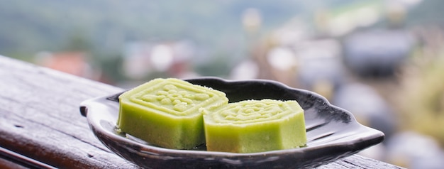 Köstlicher grüner mungbohnenkuchen mit schwarzem teeteller auf holzgeländer eines teehauses