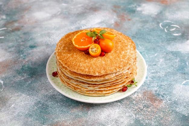 Köstlicher hausgemachter crêpe-kuchen, dekoriert mit granatapfelkernen und mandarinen. Kostenlose Fotos