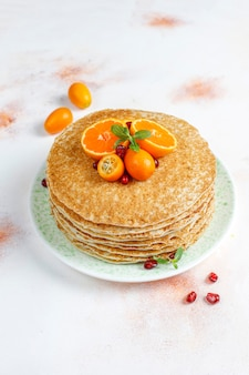 Köstlicher hausgemachter crêpe-kuchen, dekoriert mit granatapfelkernen und mandarinen.
