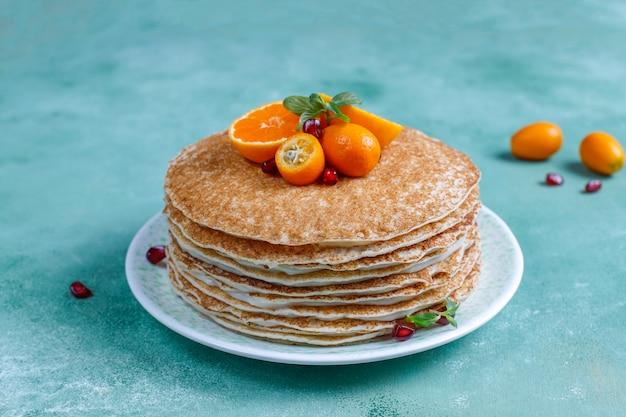 Köstlicher hausgemachter crpe-kuchen, dekoriert mit granatapfelkernen und mandarinen.