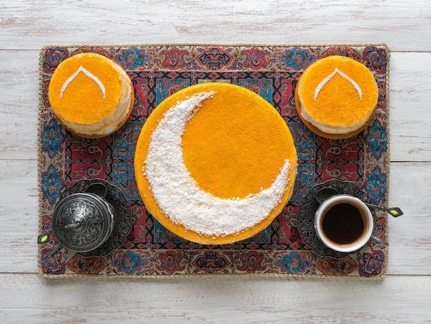 Köstlicher hausgemachter goldener kuchen mit halbmond, serviert mit schwarzem kaffee. ramadanwand