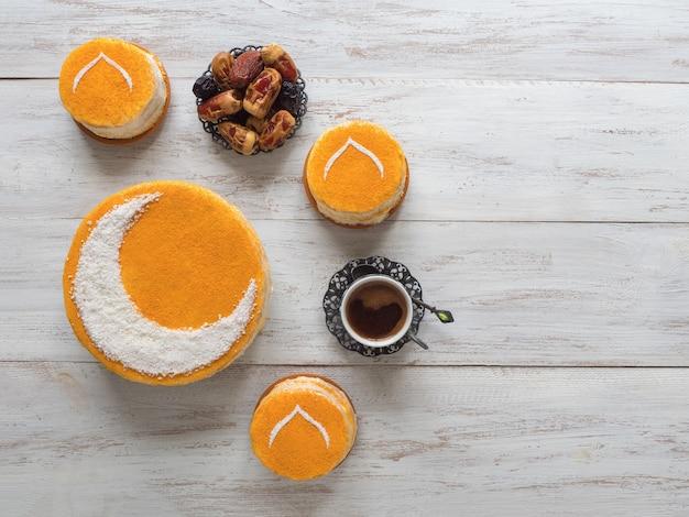 Köstlicher hausgemachter goldener kuchen mit halbmond, serviert mit schwarzem kaffee und datteln. ramadanwand, kopierraum