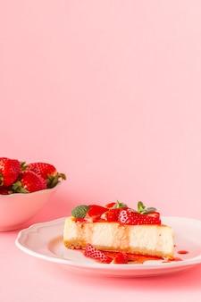 Köstlicher hausgemachter käsekuchen mit erdbeeren auf rosa.