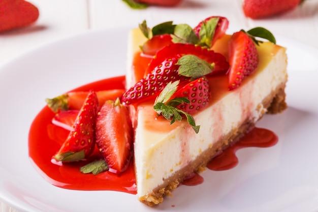 Köstlicher hausgemachter käsekuchen mit erdbeeren auf weißem holztisch.