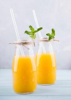 Köstlicher hausgemachter orangensaft mit strohhalmen
