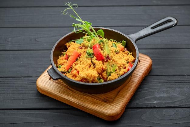 Köstlicher hausgemachter vegetarischer bulgur, couscous, mit gemüse: tomaten, karotten, zucchini, brokkoli und petersilie in rustikaler holzschale - gesundes vegetarisches essen