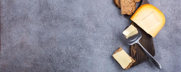 Köstlicher holländischer goudakäse mit käsescheiben, mehrkornbrot und speziellem messer auf altem hölzernem brett.