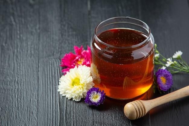 Köstlicher honig auf dunkler holzoberfläche