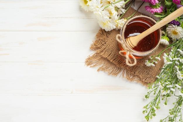 Köstlicher honig auf weißer holzoberfläche