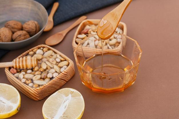 Köstlicher honig der nahaufnahme mit nüssen und zitrone