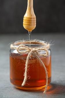 Köstlicher honig mit hölzernem honigschöpflöffel auf dunkler oberfläche