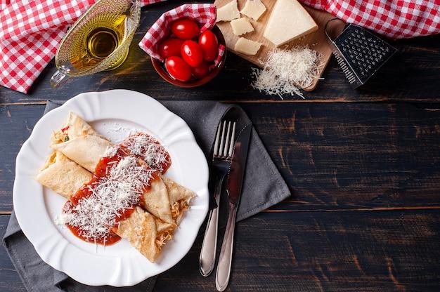 Köstlicher hühnchenpfannkuchen, gefüllt mit hühnchen und garniert mit tomatensauce und parmesan