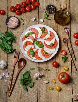 Köstlicher italienischer caprese-salat mit reifen tomaten, frischem basilikum und mozzarella