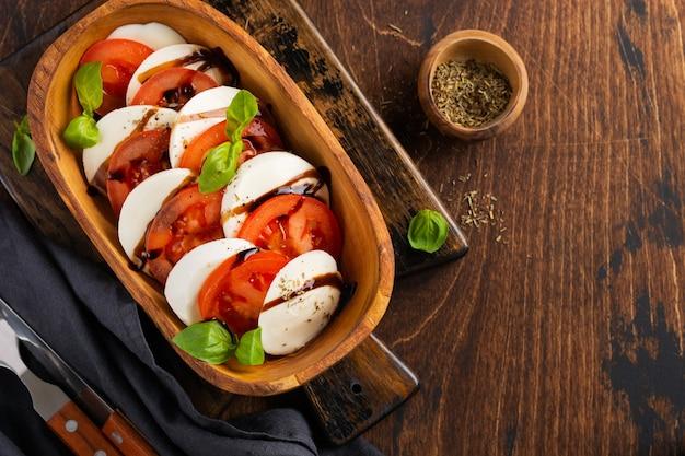 Köstlicher italienischer caprese-salat mit reifen tomaten, frischem gartenbasilikum und mozzarella-käse in olivenholzschale auf alter rustikaler oberfläche