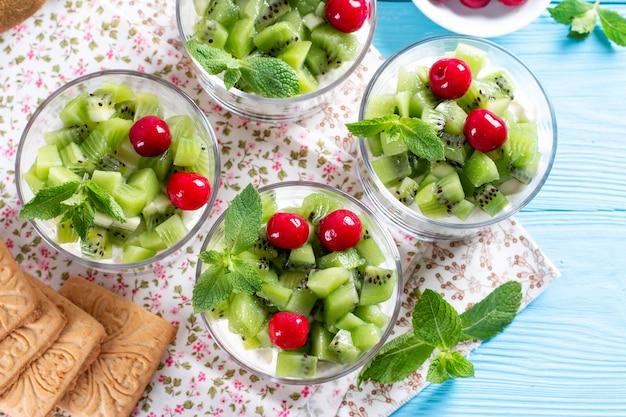 Köstlicher joghurt mit keksen, kiwi und mandeln in einem glas auf blauem holzhintergrund